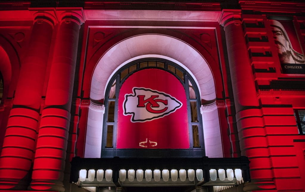 Building lit up in red lights with Kansas City Chiefs flag hanging from it