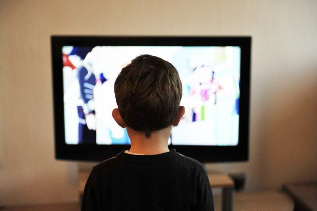 A child, facing away from the camera, watches television. The screen is washed out and we cannot see what he watches.