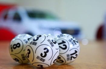 Three white bingo balls with black numbers on them, on a table.