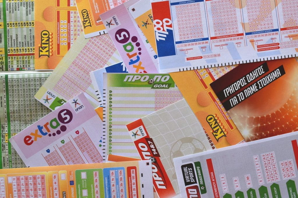 A number of different kinds of lottery tickets laid out on top of each other.