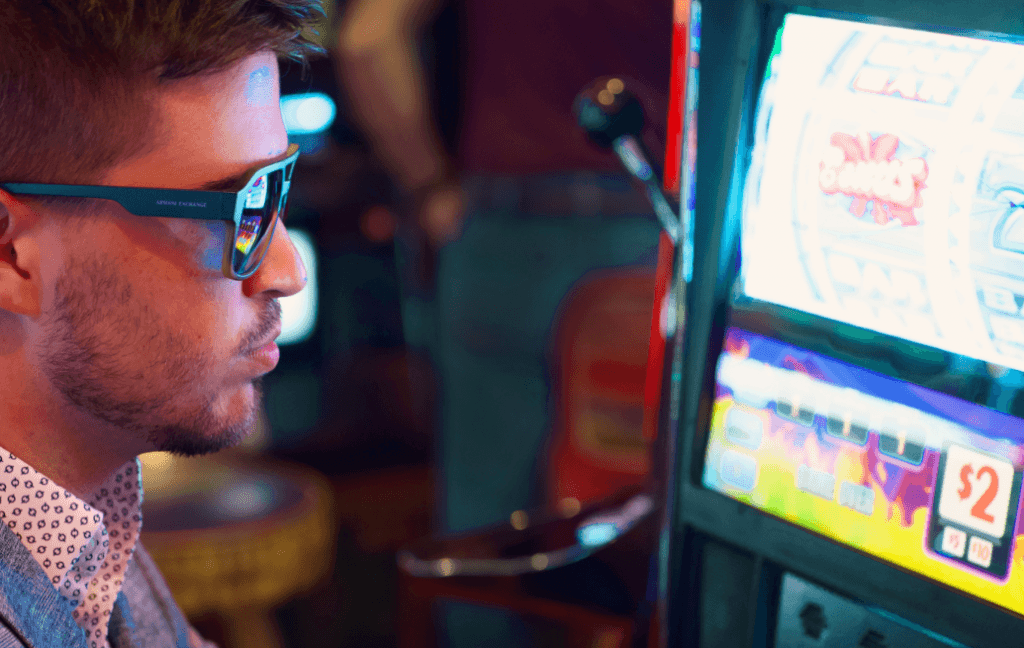 A man wearing sunglasses and a suit sits at a slot machine.