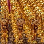 Golden Oscars winner statues lined up in rows.