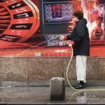 A man hoses down the street in front of an ad which includes a roulette wheel and a slot machine.