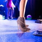 A woman wearing sparkly high heels standing on a stage.