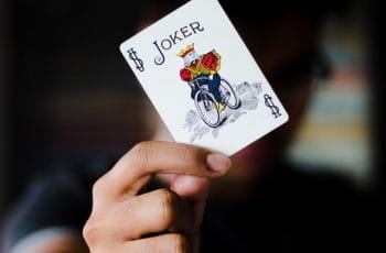 Person holds up a joker playing card in front of their face.