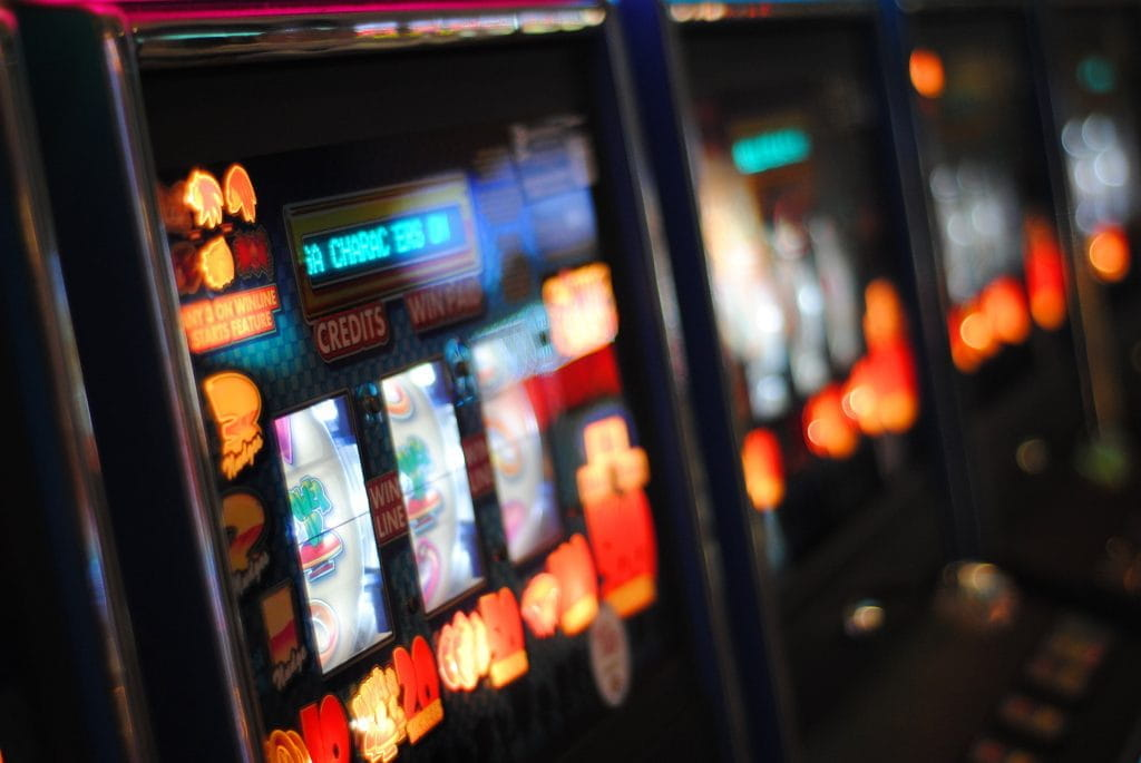 Bright colorful lights on a row of slot machines.