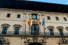 Three flags hang from a building in Spain, including the Spanish flag.
