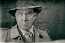 A stereotypical mobster, in trench coat and hat.