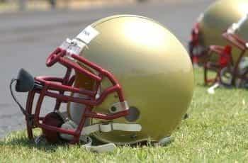 A gold American football helmet on the grass.