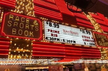 Exterior of casino with sports book advertised in neon letters.