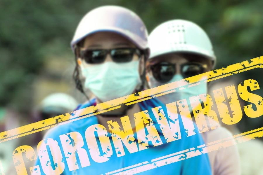A yellow stamp reading CORONAVIRUS overlays an image of two people wearing baseball caps, sunglasses, and protective medical face masks.