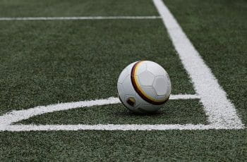 A football at the corner of a pitch.