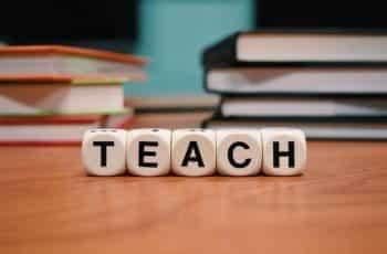 Letter blocks spelling out teach on a school desk.