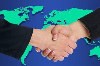 Two white hands wearing suit jackets being shaken superimposed over a colorful graphic of a map of the world.