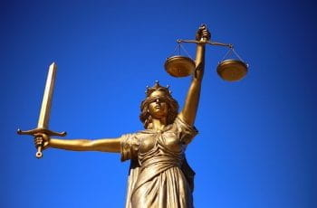 A statue of justice outside of a courthouse.