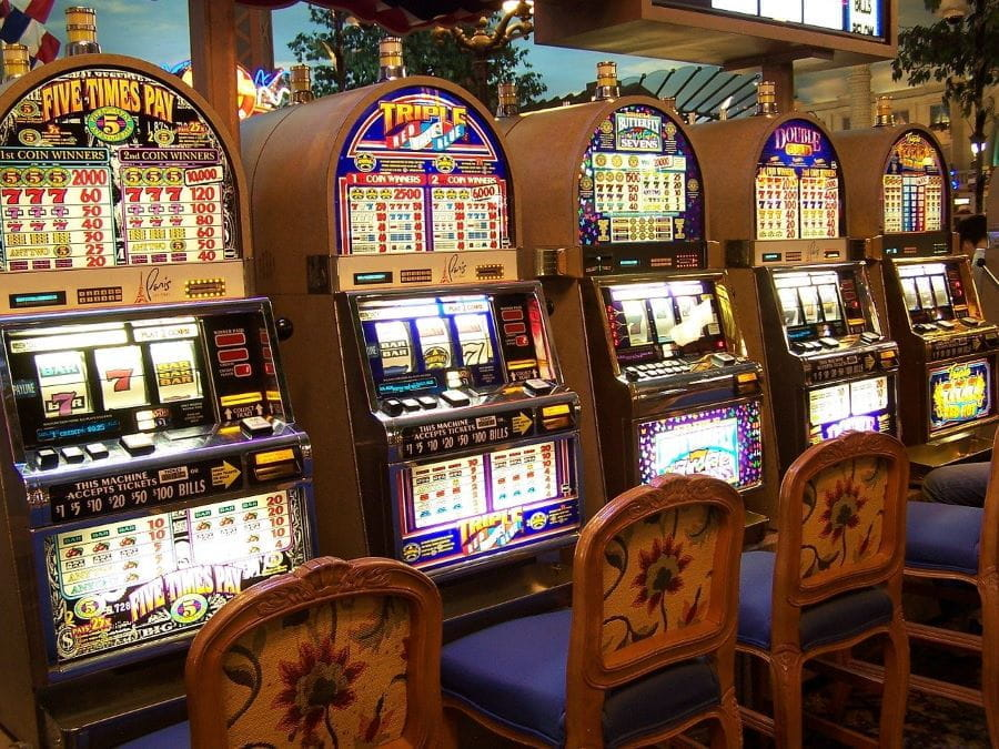 A row of three different slot machines await to be played in a casino.