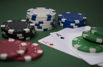 A pair of aces surrounded by stacks of poker chips.