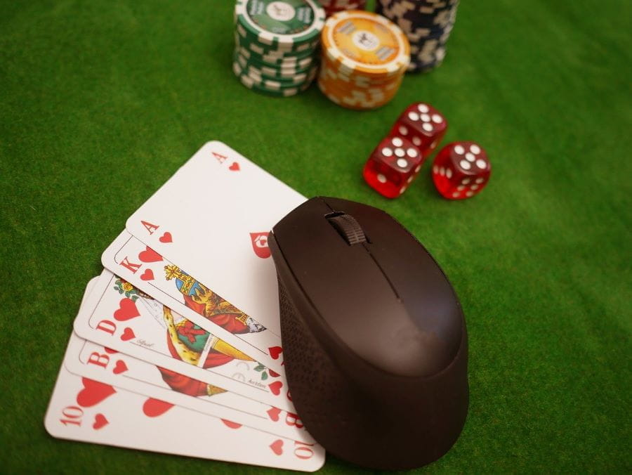 A computer mouse is stacked with poker chips, dice and playing cards.