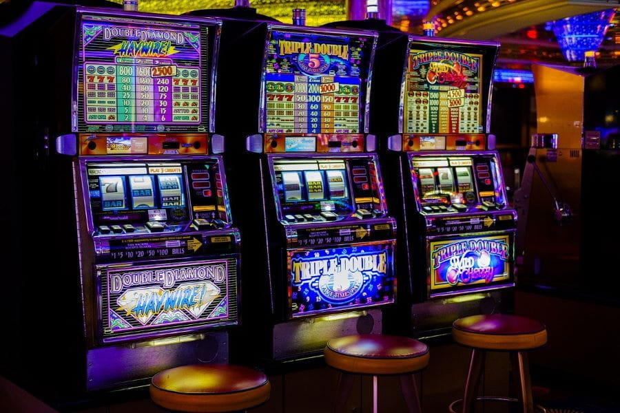 Three slot machines in a row in a casino.