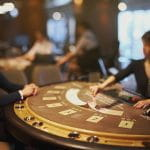 A blackjack casino worker deals cards.