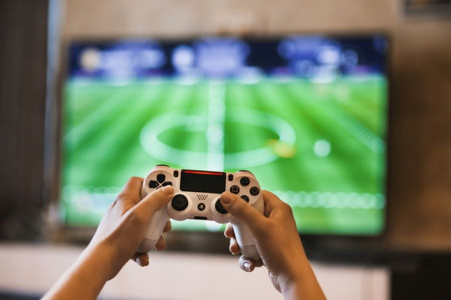 Two hands hold up a gaming controller as the FIFA video game plays in the background.
