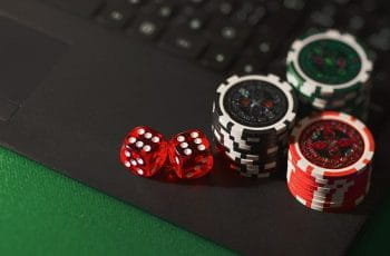 Dice and poker chips on a laptop.