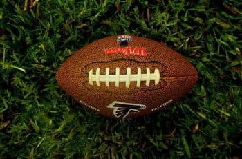 NFL football ball for Atlanta Falcons sits on grass.