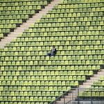 One person sitting in an empty stadium.