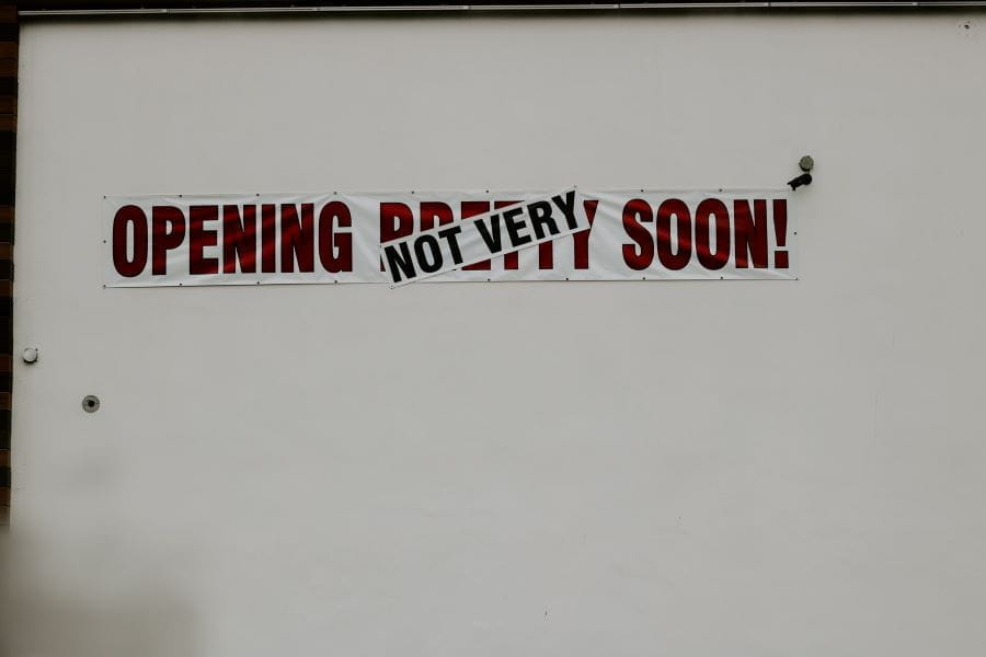 A white wall with a sign reading OPENING NOT VERY SOON.