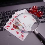 A magnifying glass on top of playing cards and a laptop next to some dice.