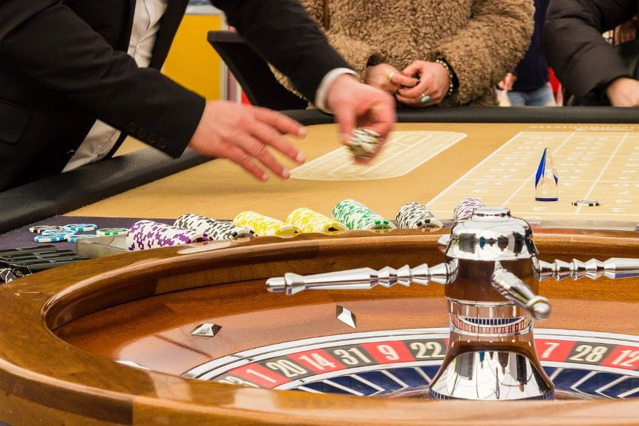 A player lays down chips at a roulette wheel.