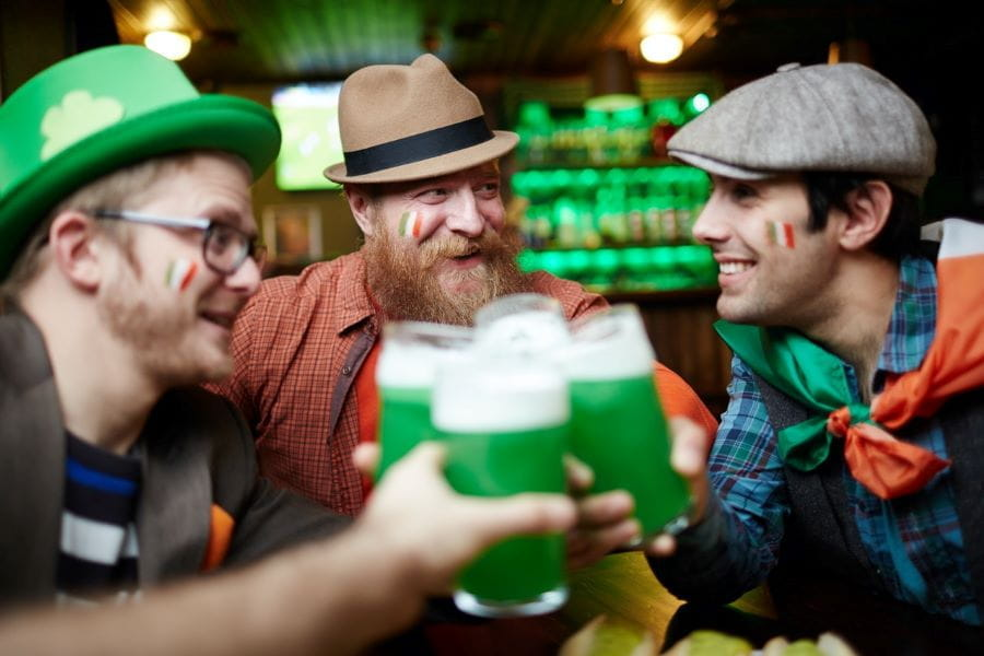 Three men with Irish flags painted on their cheeks cheers with green beers to celebrate St. Patrick's Day.