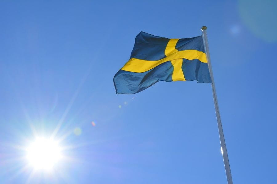 The Swedish flag flying with the sky and sun in the background.