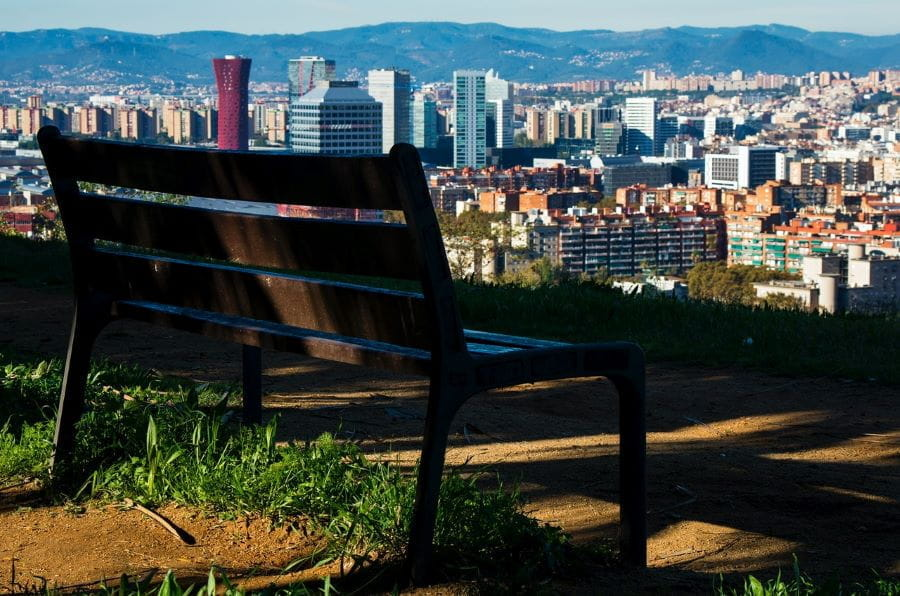 An empty bench overlooks Barcelona's skyline.