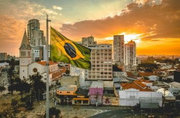A Brazilian flag flying in front of a city skyline at sunset.