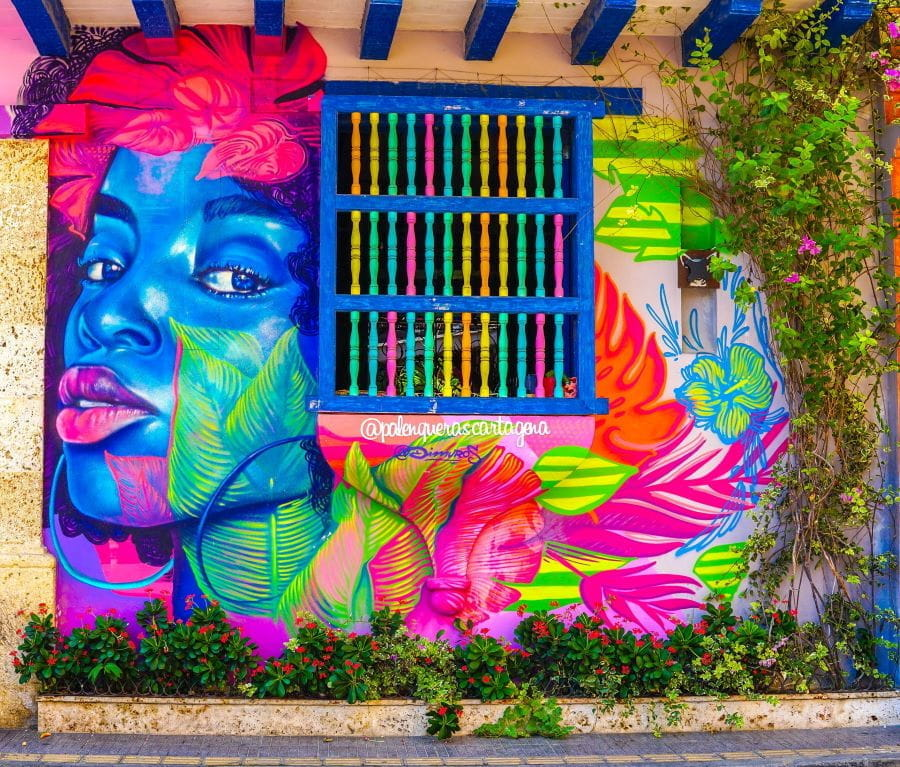 A colorful mural of a woman on a wall with barred windows in Cartagena, Colombia.