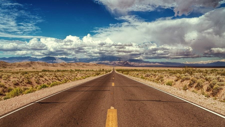 A road going through a Nevada desert.