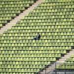 One football fan sitting in a stadium alone.
