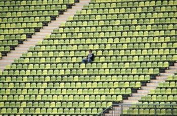 One football fan sitting in a stadium alone.