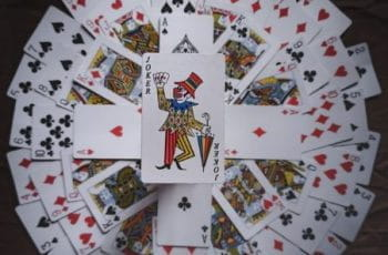 A circle of playing cards with a joker in the middle.