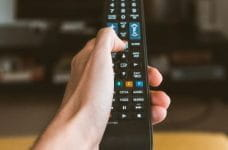 Hand holding a remote control pointed at a television.