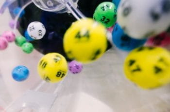 Colorful numbered lottery balls fall through the air.