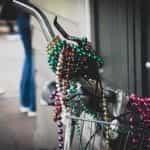 Mardi Gras beads draped around the handlebars of a bike.