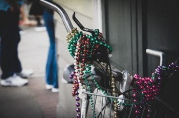 Mardi Gras beads draped around the handlebars of a bike.