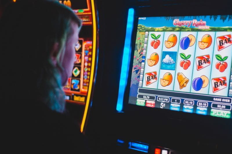 Person playing a brightly colored slot machine in a dark casino.