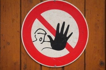 A warning sign with someone holding their hand out on it.