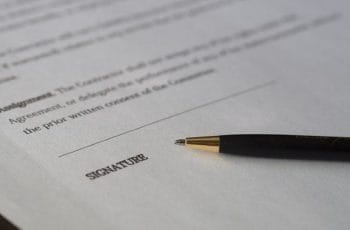 A pen lying on top of a contract.