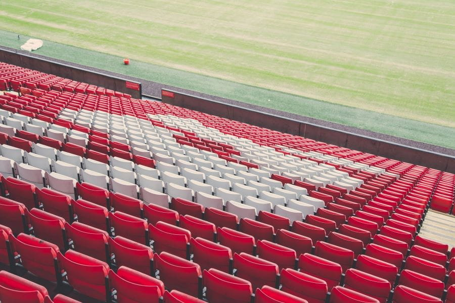 Empty red and white seats at a football stadium.