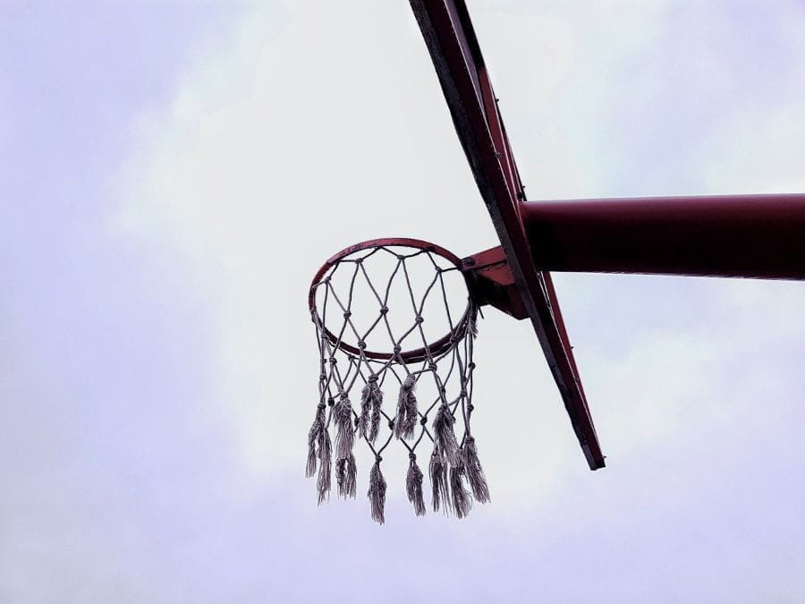 A tattered basketball net hangs in front of gray sky.