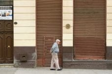 A man walks past a closed storefront in Valparaíso, Chile.